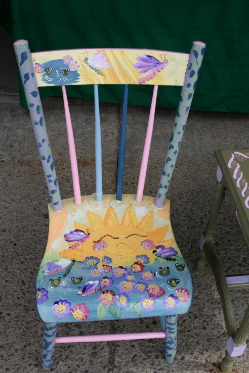 I want to like this.  I really do.  The happy face flowers have a strange appeal, and there is that whole Teletubbies sun thing going on.  But it would creep me out to sit on this chair, for sure.