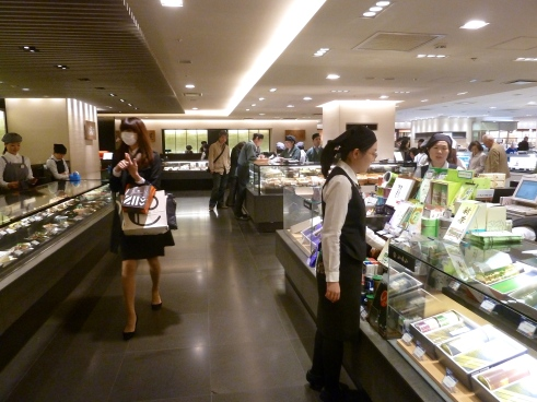 Isetan department store food halls.  See the woman walking on the left?  She is wearing a surgical face mask.  About 10% of the people you see have one on, both in offices and out on the street.  They are trying to prevent sickness, or in the case of someone who is already sick, they are protecting other people.