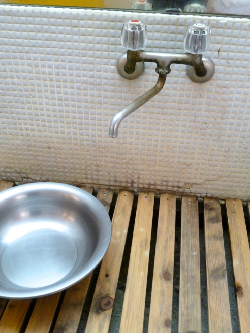 And this fairly rustic sink and bathroom with sweet little touches like the wooden drainboard.
