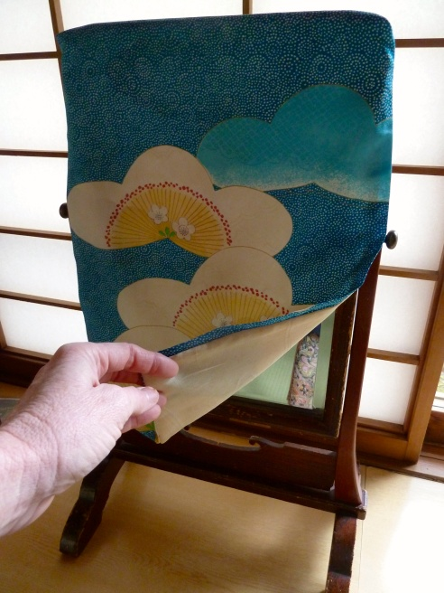 Every ryokan I've stayed in shares the common feature of a simple spare tatami mat room with various niches for storing things and displaying art or flowers.  But I appreciate their subtle differences, and additions, like this mirror covered with a silk fabric print.