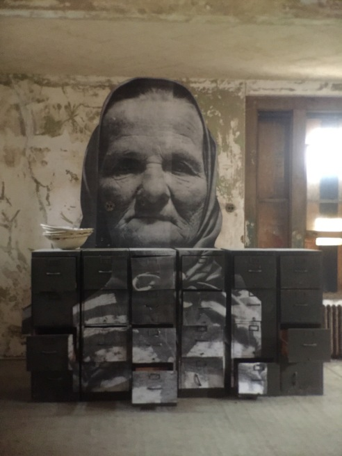 """The French artist JR has masterfully applied actual photos of Ellis Island immigrants onto the decaying surfaces. I loved the story about this woman. When she met a US official he asked her a standard question to test her mental acuity. """"If you are hired to clean stairs, is it correct to start cleaning at the top or the bottom."""" This feisty person answered, """"Sir, I did not come to America to clean stairs."""" She passed the test with flying colors."""